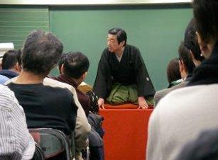 黒板を背にし講座ならぬ高座で八五郎出世を聴かせる鳳楽師匠